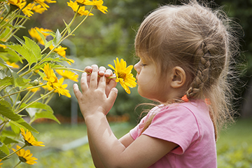 Girl sniffing yellow flower
